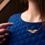 Collier 3 poissons finition or porté sur un pull bleu - Les Naturalistes bijoux