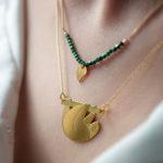 Collier paresseux finition or porté en accumulation, ambiance forêt - Les Naturalistes bijoux