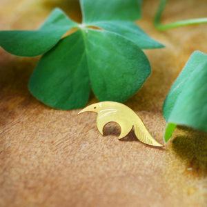 Pins tamanoir finition or avec un trèfle sur une table en bois- Les Naturalistes bijoux